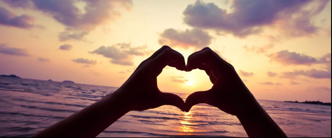 Fingers forming a heart with sunset in background